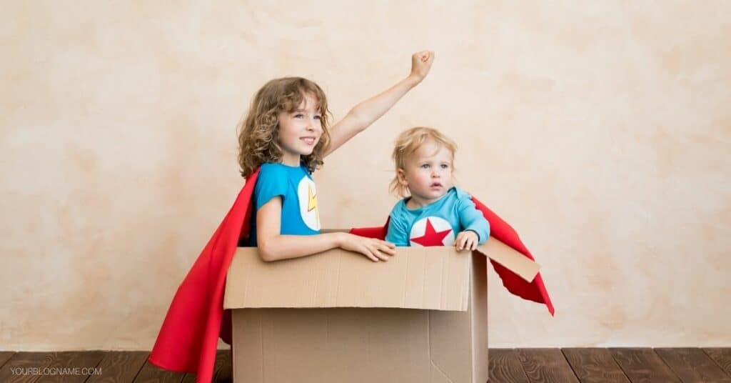 A toddler and older child doing pretend play with a cardboard box.