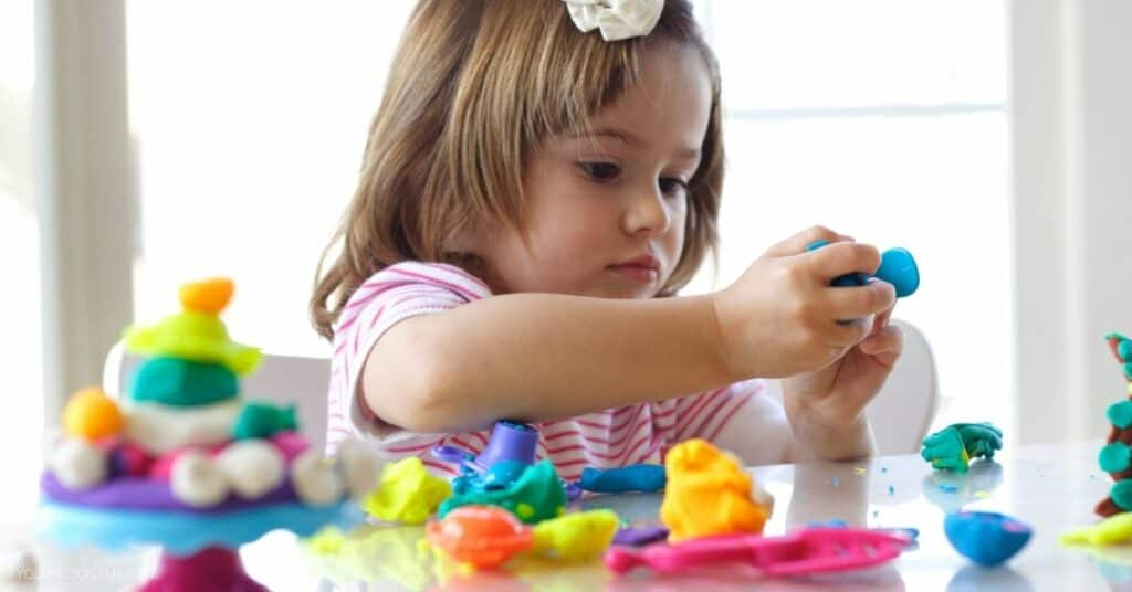 Toddler plays with different kinds of toys (such as play doh and some plastic bows and utensils).