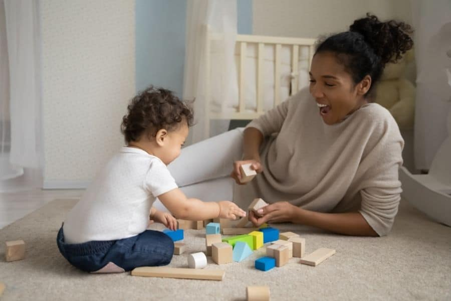 mom shows toddler how to play with blocks, while laughing and talking together