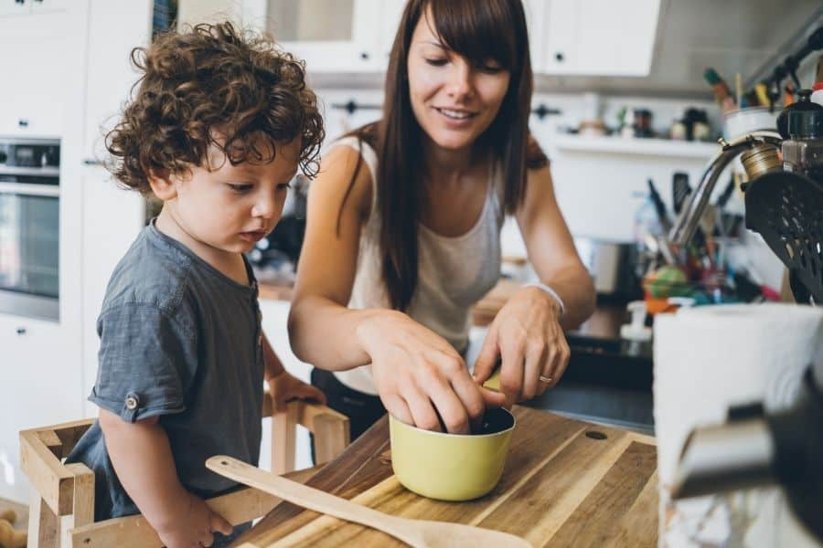 young child helping mom in kitchen
