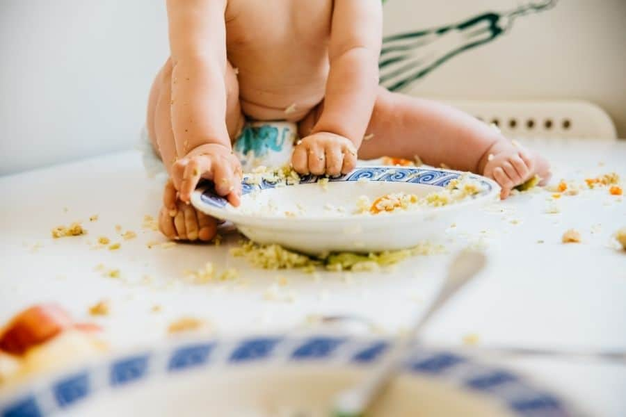 baby eating messily, showing it's okay to make a mess
