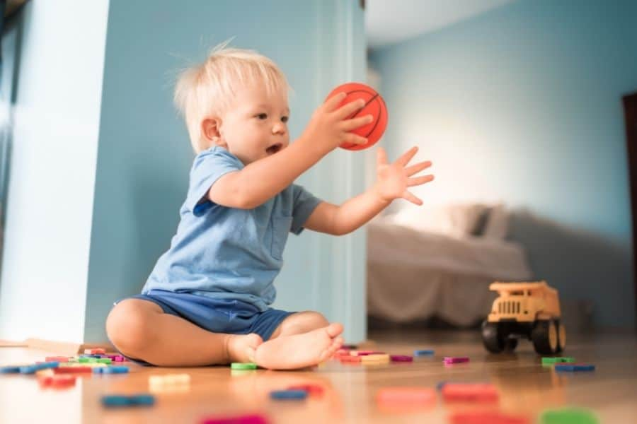 toddler playing with a ball, developing motor skills